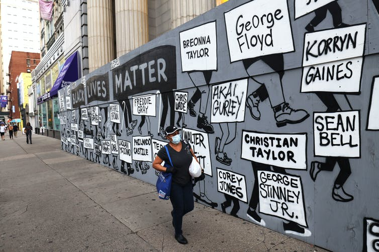 Woman walks past a Black Lives Matter mural