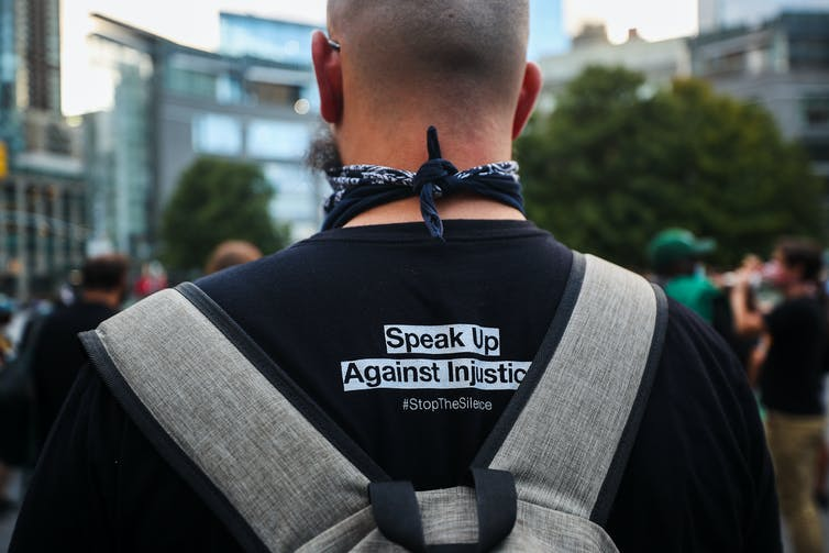 Back of a man whose t-shirt reads 'Speak up against injustice'