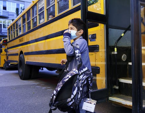 A boy stepping off a school bus carry a backpack and adjusting a blue face mask.