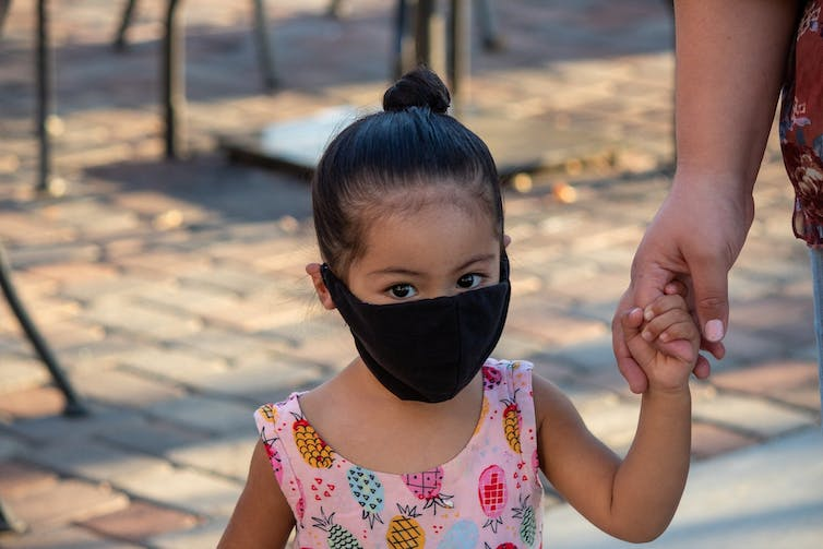 Little girl in a pink dress wearing a black face mask holding the hand of an adult who is out of the frame.