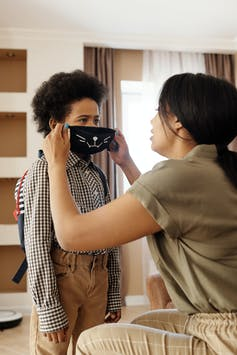 A woman puts a mask on a child, who is wearing a backpack and appears to be ready for school. The mask has a cat whisker motif.