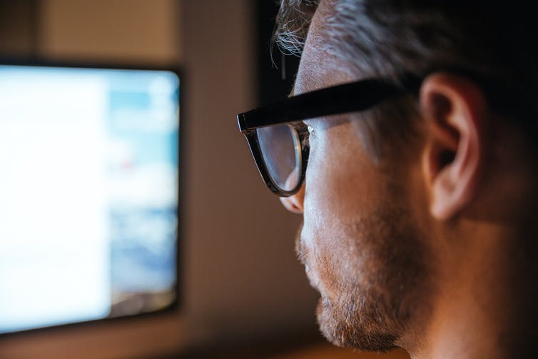 Profile of man looking at blurred computer screen.
