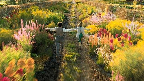 Film still: two children run through a flowering garden