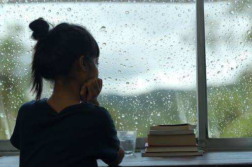 Young girl looking out the window on a rainy day
