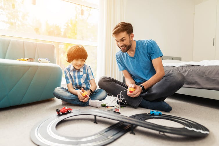 Father and son racing a toy train on a track.