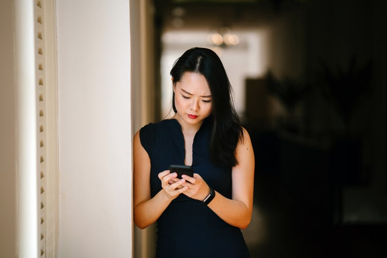 Woman looking at her phone with serious expression.