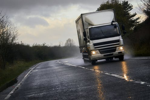 A white lorry speeds down a wet road.
