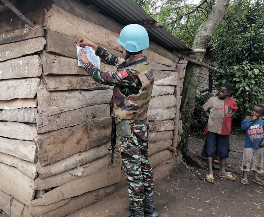 Man in blue helmet pins poster to wall of wooden house with two children looking on.