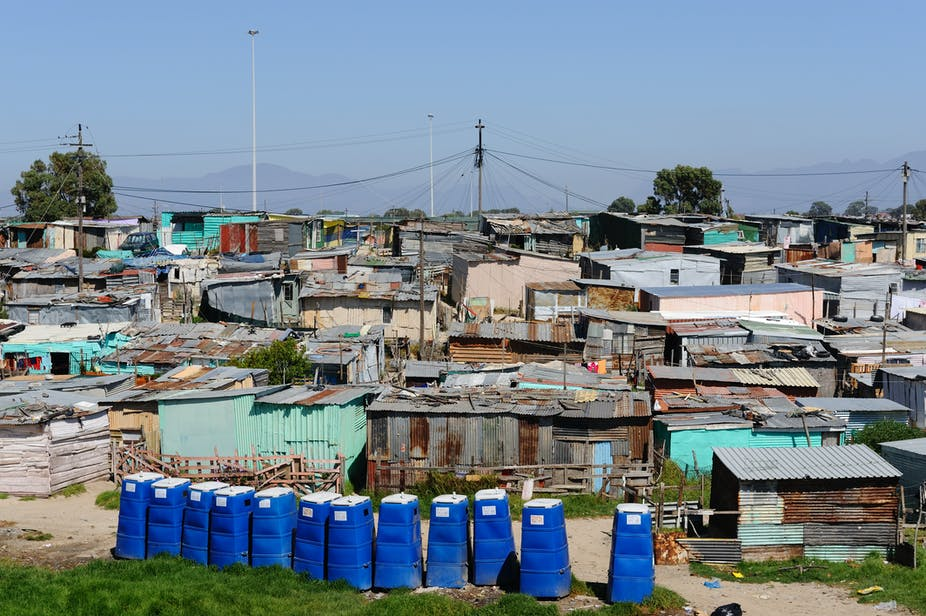 A row of blue, portable toilets on the outskirts of an informal settlement