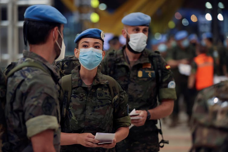 Three soldiers in blue berets wearing face masks.