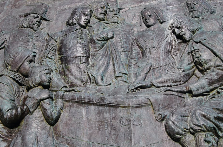 Sculpture of group of men and women signing a document.