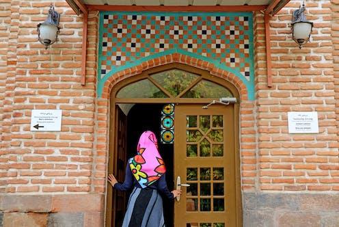 A woman enters a mosque.