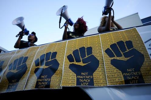 Black lives matter activists speaking while protesting.