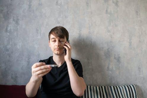 Un hombre habla por teléfono mientras observa un termómetro.
