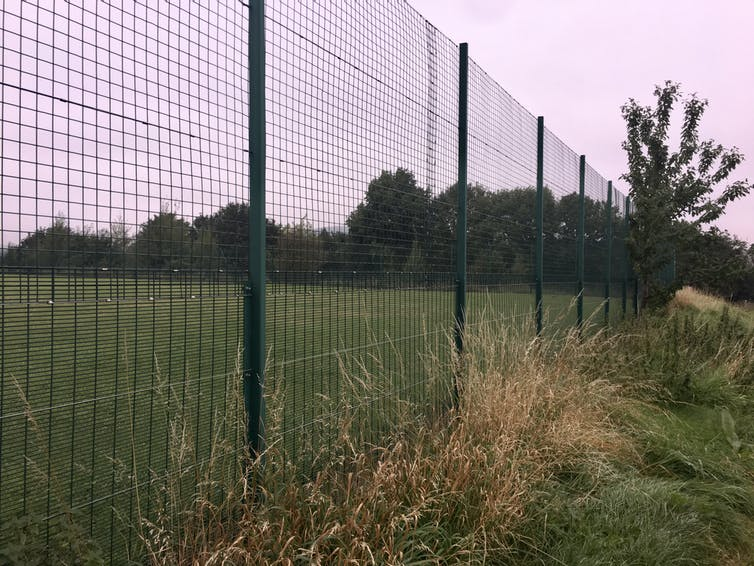 Chain link fence separating sports pitch