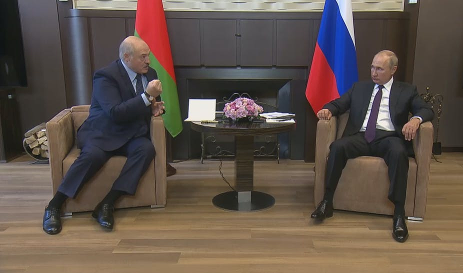 Alexander Lukashenko and Vladimir Putin sitting in chairs with their flags behind.