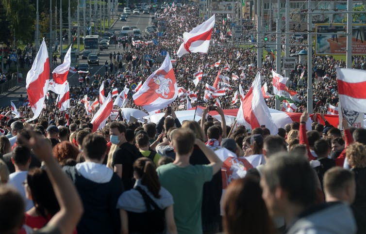 Large crowd of Belarusian protesters waving flags.