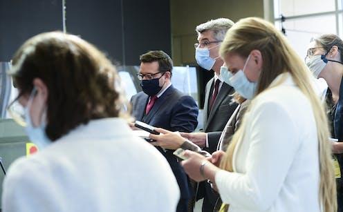 Journalists wearing masks in a media scrum.