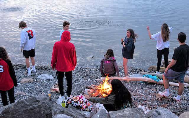 Teenagers meet around a campfire at Lake Champlain.