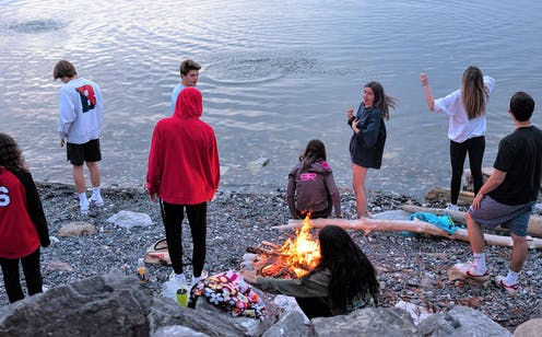 Teenagers meet around a campfire at Lake Champlain.