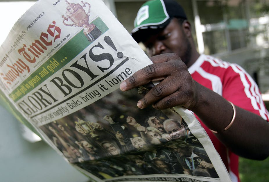 A man wearing a green sports cap and read T.shirt reads a copy of South Africa's Sunday Times