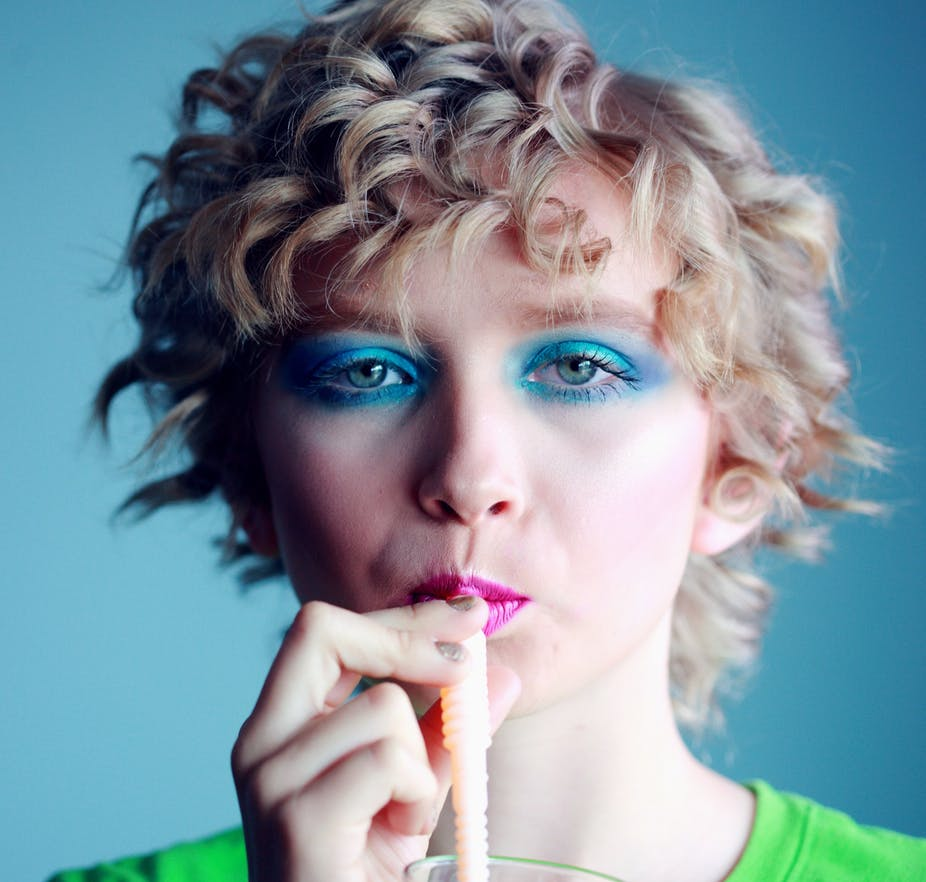 Woman with blue eye shadow drinking from straw