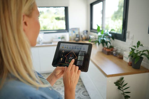 A woman looks at a smart energy system on an iPad in her home.