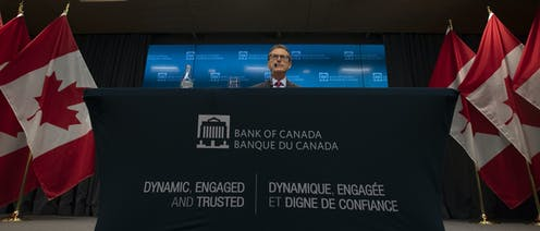 A man sits behind a dais reading Bank of Canada, with Canadian flags on either side.