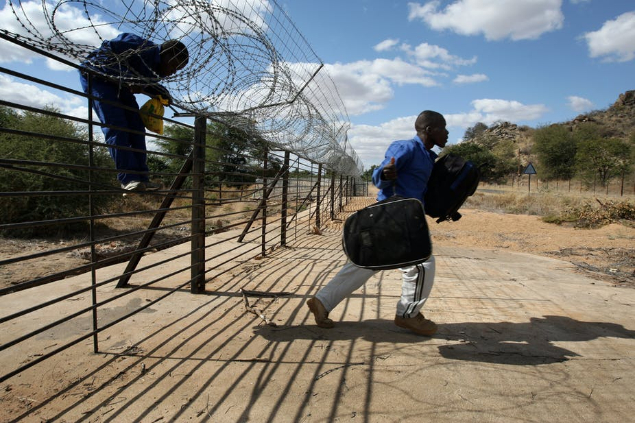 A man carries a backpack after jumping a barbed wire fence marking the border between South Africa and Zimbabwe while another prepares to join him