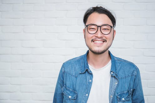 Young Asian man wearing glasses.