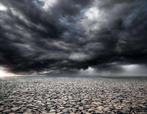 Dark storm clouds over a parched landscape.