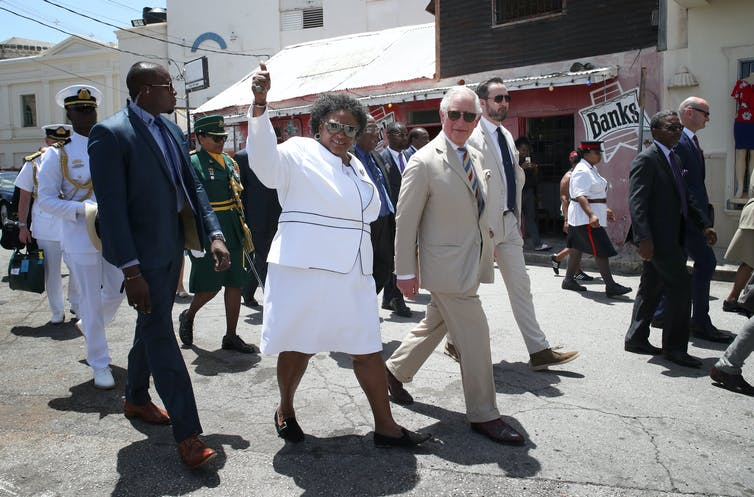 Mia Mottley and Prince Charles walking in a group of other people.