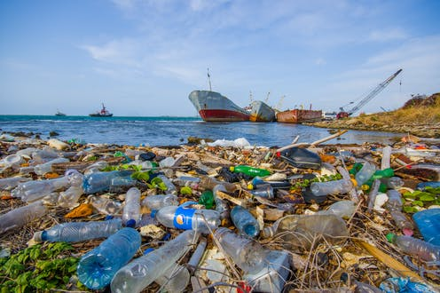 Plastic litter floats on sea surface, large ship in background