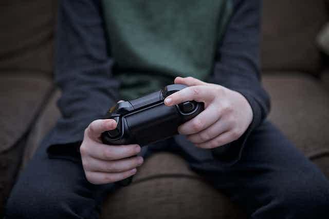 un niño con un mando de videoconsola en las manos.