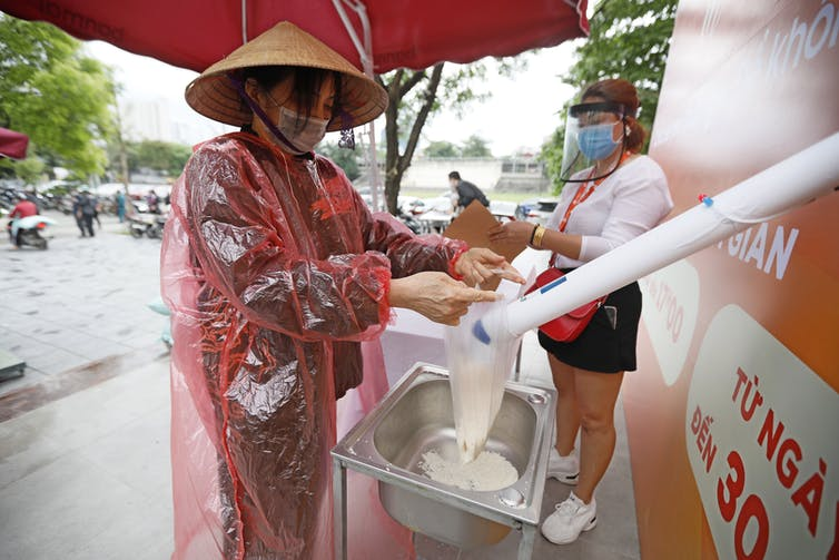A woman in a pointed hat and rain poncho collects rice from a dispensing machine.