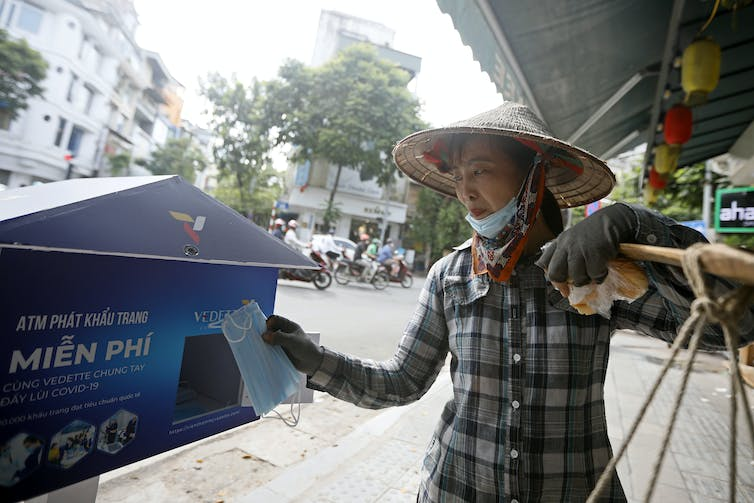 A woman wearing a pointed hat collects a mask from a street machine.