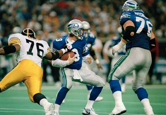 a football player grabs another player from the opposing team while a third football player watches