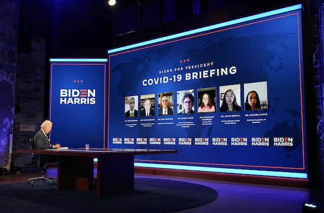 US Democratic presidential candidate Joe Biden sitting on stage, heading a COVID-19 briefing