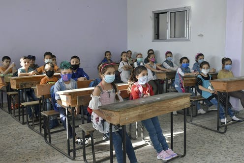 Syrian children wearing face masks in a classroom
