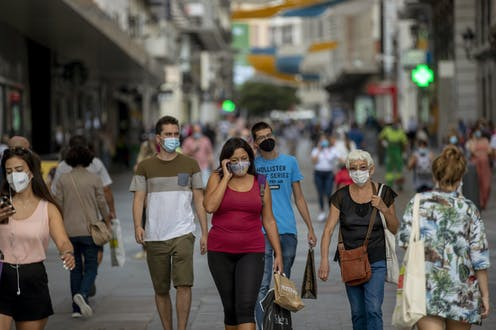 People wearing face masks while walking city streets