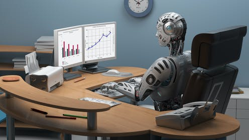 A robot sitting at a desk in front of a computer.