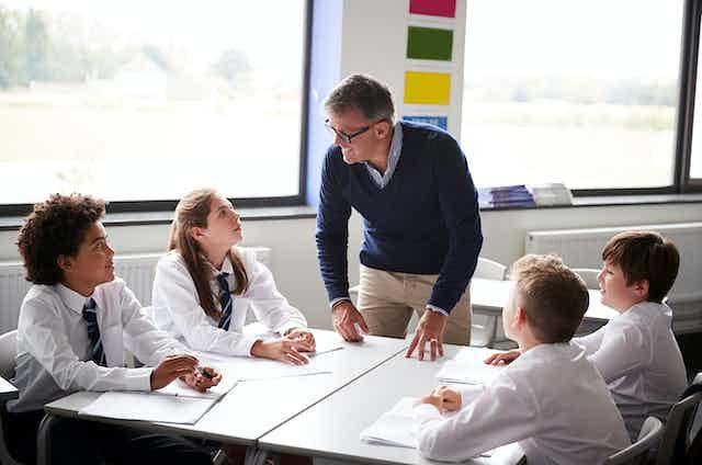 A high school teacher speaks to students.