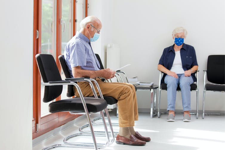 A man and a woman wearing masks sit in a waiting room.