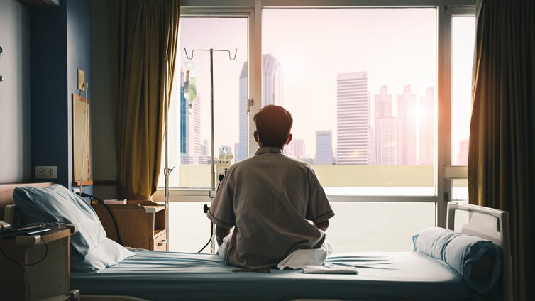 A man sits on his hospital bed looking out the window.