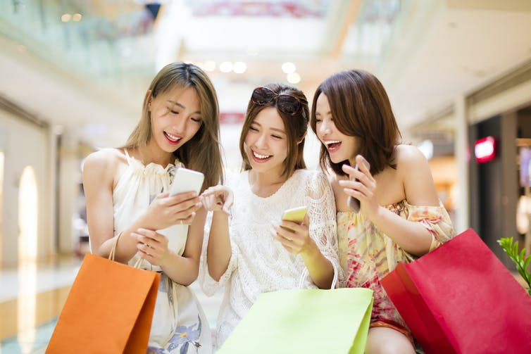 Three women smiling at smartphone in shopping mall.