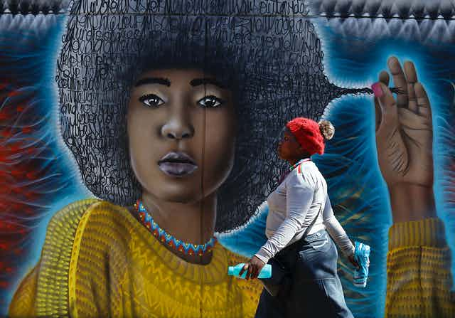 A woman walks past a street art mural showing a young woman with an Afro hairstyle comprised of squiggles, pulling at a lock of it.