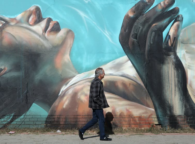 A man walks past a street art mural depicting a blonde-haired woman lying calmly on her back underwater.