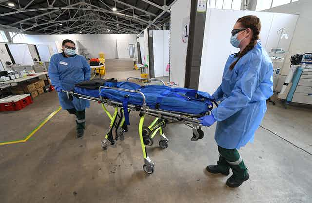 Two ambulance volunteers push a stretcher
