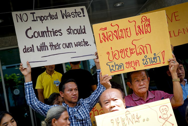 Man holds sign saying 'No imported waste! Countries should deal with their own waste'