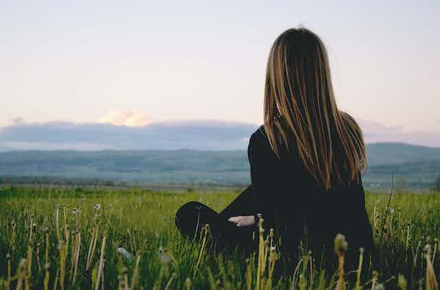 Woman sitting alone in field.